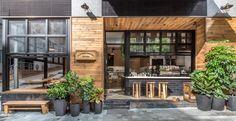 壁際に縁側的なベンチシートのある開放的なカフェのダイニングと右サイドのカウンター席 正面から
