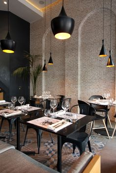 Black is used boldly in this restaurant with brick walls patterned tiles