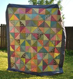 """The final dimensions are about 95"""" by 85"""" with the grey border. I made HSTs with Denyse Schmidt's """"Hope Valley"""" collection and used a pale yellow flat sheet for the back. With my left over fabric, I made a pieced binding and a matching pillow."""