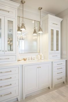 White on white bathrooms can be anything but boring.  I frequently do adaptations of this style.  I prefer to mount sconces to the mirror however because I feel hanging pendants compete with the upper cabinets.  I also use a recessed LED can light over the sink in all bathrooms to provide great, unobtrusive lighting.