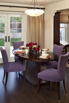 Custom oval shaped walnut table and metal base from Murray's Ironworks. Dining chairs with amethyst colored faille fabric from Gaul Searson. by Lindy Donnelly