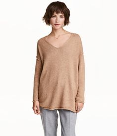 Beige melange. Fine-knit sweater in a soft cotton blend with wool content. V-neck, dropped shoulders, and long sleeves. Roll edges at cuffs and hem.