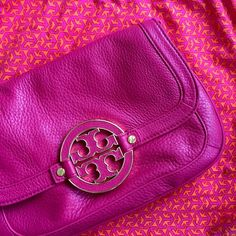 Tory Burch Amanda Logo Clutch Tory Burch Amanda Logo Clutch in magenta. Genuine leather with gold-plated logo. Top flap opening with magnetic closure. Removable, adjustable strap included. Interior zip compartment. Measures 19 x 29 x 4 cm. Tory Burch Bags Crossbody Bags