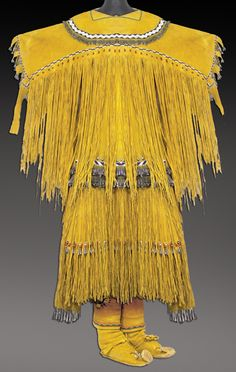 "Traditional yellow ochred buckskin Sunrise dress/skirt, shoulder yoke, and high top moccasins with toe tabs, all done with great detail including cutouts, German silver buttons, fringe, and tin cones. Moccasins 9"", skirt 34"", blouse 33"" x 42"""