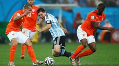 Lionel Messi of Argentina is challenged by Jordy Clasie and Georginio Wijnaldum of the Netherlands