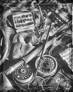 A whole pile of fly fishing gear.  A nice picture in black and white, you can see the contrasting textures.