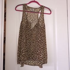 Cheetah Print Sleeveless Top Chiffon sleeveless top with button up front. Can be worn alone or under a blazer or cardigan to add some glam to any outfit! Garage Tops Tank Tops