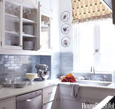 A backsplash of blue-gray Metro subway tile is paired with white cabinets in this small but distinctive Park Avenue kitchen designed by Daniel Sachs.