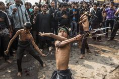 Shiite boys strike themselves with sharpened blades attached to chains as part of a self-flagellation ritual during a religious procession marking Ashura on November 25, 2012 in New Delhi, India. The religious festival of Ashura commemorates the seventh-century martyrdom of Prophet Muhammad's grandson Imam Hussein in the battle of Karbala. (Getty Images) #news #photography #religion