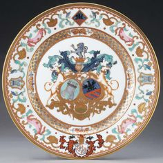 A Limoges Porcelain Armorial Plate. after the Chinese service of 1736, Arms of De La Bistrate, Proli and Boone, painted by Michael Meinopreo, painted in gold, silver, green and red enamels with the Arms of De La Bistrateof Anvers in Brabent accollee with Proli of Milan and Grabent, and on the rim with the Arms of Charles Boone, the cavetto reserved with four floral panels on a ilt trellis diaper band, the rim painted in famille rose enamels with flowers aand foliage. France, circa 1801-1900