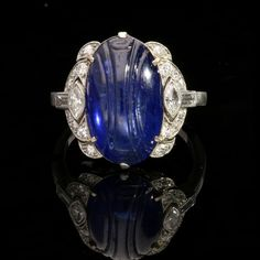 ART DECO 8.64ct BURMA OVAL ENGRAVED CABOCHON SAPPHIRE RING c.1925.  Mounted in platinum with marquise, baguette & single cut diamond shoulders.