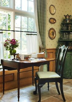 An antique Pembroke table and Chippendale chair form a lovely spot for morning tea in this kitchen - Traditional Home® / Design: Jack Fhillips / Photo: Robert Brantley