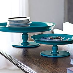 Teal Pedestal Trays  A blast of electric color turns a traditional Thai-inspired offering tray into a coffee table centerpiece. Carved by hand out of wood with a high-gloss, spill-proof surface that's friendly to candles and cocktails alike.