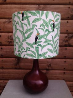 The Linen blended fabric covering this lampshade is from South Korea. It is a pale white background with tropical leaves and Toucans.  The