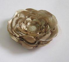 Flor em cetim marrom claro com camadas de chiffon. Pode ser usada como acessório de cabelo ou como enfeite de roupas, bolsas, etc.