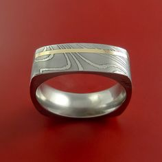 This 7mm wide DAMASCUS SQUARE Ring has a Wood Grain Pattern and a MIRROR POLISH FINISH. There is a 1mm wide 14K YELLOW GOLD inlay that encircles the entire ring. Each ring is custom made and the pattern unique, so no two rings are exactly alike. Damascus Steel rings are very desirable. Your ring comes with a COMFORT-FIT for extra satisfaction. Our DAMASCUS ring WILL NOT RUST OR TARNISH. Style (DS14YQ01)Damascus steel is an ancient art form. This blacksmith alloy is made using two types of…