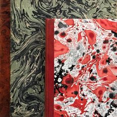 The marbled covers of an over sized 1911 German book with a smaller 1944 Danish book.