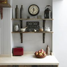 Vintage style kitchen design idea: reclaimed shelving and repurposed antiuques. Love the antique clock and vases!