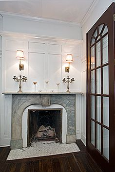 Upon entering this famous NYC townhouse from the street, you immediately notice the hardwood floors and ivory wall moldings. The front dining room is smartened by decorative paneling and a gas fireplace with a stone mantelpiece.   #entry #fireplace #townhouse #brownstone #realestate #interiordesign