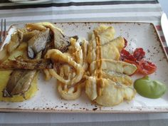 """Franxerra Restaurante: thick cut homemade potato chips topped with oyster mushroom, squid rings, and fish with 3 sauces, and slightly dried tomatoes. Creative and """"rico."""""""