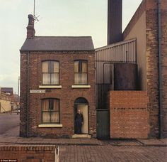 A dripping-refinery worker, poses outside his home next to the factory he'd worked at for 12 years, on Vulcan Street (Leeds) in 1975.