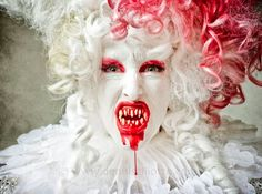 The blood dyed wig and the parts of the face red with the rest white. The teeth are what make the whole thing, I would see this as a succubus look.