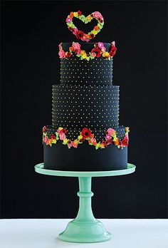 Brides.com: 21 Wedding Cakes for Dark, Modern Color Palettes. A Black Fondant Wedding Cake With Flower Garlands. How stunning is this three-tier confection from Wild Orchid Baking Company? Edgy black fondant feels fun, not severe, thanks to whimsical bright green dots and gorgeous flower detailing. Planning a wedding with a Midsummer Night's Dream vibe? This is your cake!  See more black wedding cakes.