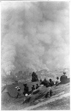 [Spectators sitting on hillside watching fires consume the city after the 1906 San Francisco earthquake]