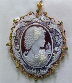 Hand-carved #cameo set in 14k gold surrounded by diamonds and emeralds. Like the additional carving around the cameo!