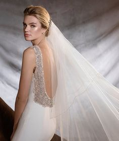 A radiant, jewel-like wedding dress in crepe and tulle embellished with gemstone decorations on the back. A flattering style, fitted to the hips, with a bateau neckline and floaty skirt. A real show-stopper!