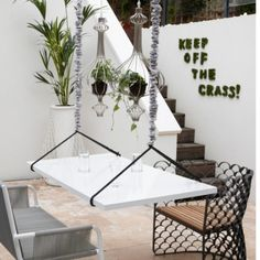 Quirky white patio garden A hanging table lit with wire pendant lights, makes an interesting change to standard garden furniture. Faux-grass lettering is used to create a fun feature wall that's in keeping with the quirky nature of this patio garden. Swing Table, Bed Table, Hanging Table, Diy Hanging, Hanging Plant, Hanging Furniture, Garden Furniture, Living Furniture, Wire Pendant Light