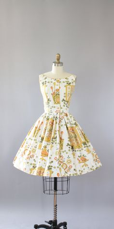 Vintage late 50s/early 60s Kay Windsor yellow floral and novelty print. Novelty print is of scenes from the kitchen, so cute! Buttons up in