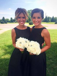 Long black bridesmaid dress with straps and pockets and white roses