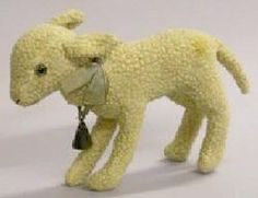 A Steiff curly mohair lamb, circa 1920s, 9 in., green glass eyes, white curly mohair fur, embroidered nose and mouth, blue neck ribbon and bell.