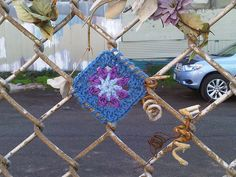 teeny yarn bomb, this would be pretty quick and easy, I should try it on the fence across our alley