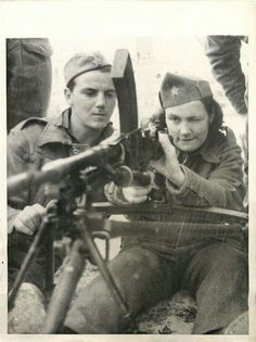 1944 - British soldier teaches a female Yugoslavian partisan how to use a Bren gun at base in Malta.