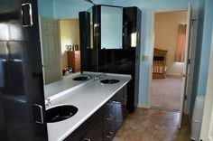 Bathroom with Jack and Jill sinks, built-in dark cabinetry and tile floor.
