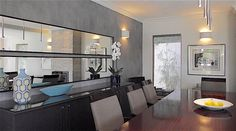 Dining room with two large horizontal mirrors against a textured wall www-in-form-design.com