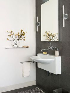 Opt for a wall-hung vanity to make a small bathroom feel open and airy. This sculptural wall-mount sink -- paired with an equally eye-catching wall-mount faucet -- offers sleek curves that stand out from the contemporary gray wall tile. Sleek medicine cabinets offer storage space above the sink and complement the bathroom's simple style.