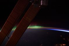 "This nighttime view of Earth's horizon and scattered city lights was photographed by one of the Expedition 30 crew members aboard the International Space Station. Activity of Aurora Borealis appears from behind one of the orbital outpost's solar array panels, then fades into an area where Earth's limb is visible and finally a small ""slice"" of daybreak appears at right."