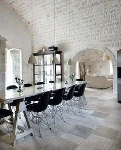 black Eames chairs surrounding a long table in a white dining room with white pendant lights, a long table and painted brick wall with arched entryway into a living room