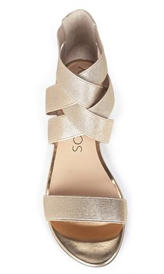 Gold metallic-coated elastic flat sandals with crisscrossing straps at the ankles and an open toe strap