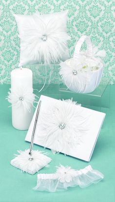 Wedding Ceremony Accessories features a six piece matching accessories set from the Feathered Flair collection. Includes flower girl basket, ring pillow, guest book, pen set, unity candle and bridal garter. Elegant white satin with white satin bands, layered feather accent and clear gem center. Set is available in white and black.