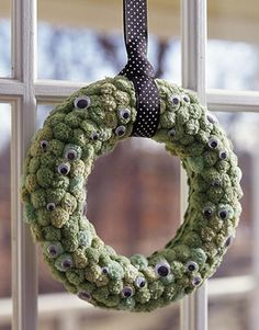 Watchful Eyes    Googly eyes eerily peer at guests as they enter your Halloween lair. Hot-glue green pom-poms to an 8-inch-diameter plastic-foam wreath. Then adhere various-size googly eyes onto the pom-poms using hot glue. Fold a length of ribbon in half. Loop the folded ribbon around the wreath and pass the ribbon ends through the loop. Tie the ends together to make a hanging loop.