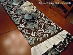 Napkins sewn together to create a table runner, with white table runner ruffle and ribbon....pretty.