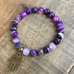 Simple yet beautiful faceted purple agate bracelet with a Hamsa hand pendant, perfect for layering! Stringed on thick hitec elastic. You may ask to have the charms removed or changed, just add a note