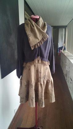 Vest voorzien van kantrand, rokzoom omhoog aangerimpeld, verwijderde strook is sjaal.