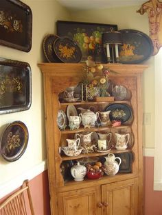 Cupboard of transferware surrounded by toleware trays.