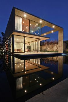 "Concrete and Glass Home ""Floats"" on Serene Reflection Pool"