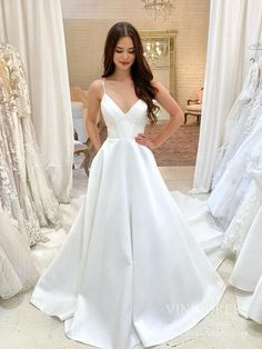 High-quality satin wedding dress with long train - Low back with zipper closure - Long train detailing with buttons all the way along the middle down to the hem - Boned bodice - Pockets on sides - Minimalist wedding dress - Ivory satin wedding gown - Cathedral train - Built-in-Bra